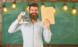 Учитель биологии в eyeglasses держит книгу и микроскоп Концепция биологии Человек с бородой на усмехаясь стороне в классе стоковое фото rf