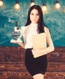 Учитель биологии держит книгу и микроскоп Концепция биологии Дама в официально носке на спокойной стороне в классе Дама стоковая фотография rf