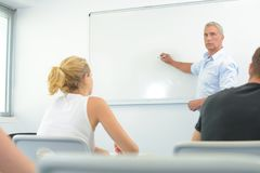 Учитель в передней белой доске в классе Стоковая Фотография