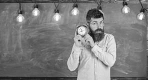 Учитель в eyeglasses держит будильник Человек с бородой и усик на сконцентрированных часах стороны слушая лучей стоковые фото