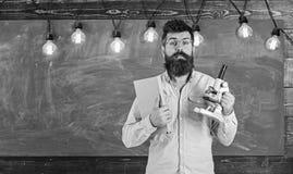 Учитель в eyeglasses держит книгу и микроскоп Человек с бородой и усик на удивленной стороне в классе научно стоковое фото rf