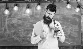 Учитель в eyeglasses держит книгу и микроскоп Человек с бородой и усик на занятой стороне концепция научного исследования стоковые изображения