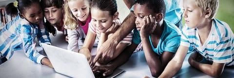 Учитель и дети используя ноутбук в библиотеке стоковое изображение rf