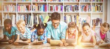Учитель и дети используя цифровую таблетку в библиотеке стоковые изображения rf