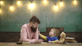 Учитель и малые письма сочинительства ребенк в тетради с прописями Милый мальчик рисуя изображение с красочными карандашами Урок  сток-видео
