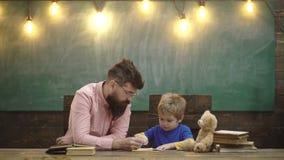 Учитель и малые письма сочинительства ребенк в тетради с прописями Милый мальчик рисуя изображение с красочными карандашами Урок  видеоматериал