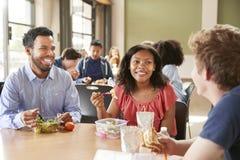 Учитель и студенты есть обед в столовой средней школы во время гнезда стоковая фотография rf