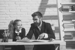 Учитель и школьница в комнате исследования на белой предпосылке кирпича Стоковое Изображение RF