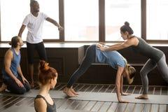 Учитель йоги помогая женщине делая вниз - смотреть на stretchin собаки стоковое фото