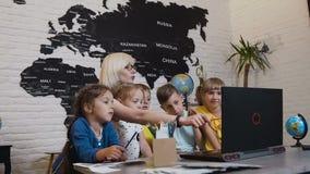Учитель молодой женщины обсуждая компьутерную программу с группой в составе зрачки Учительница используя компьтер-книжку с зрачка акции видеоматериалы