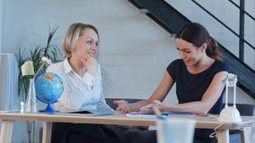 Учитель на столе говоря друг к другу Стоковые Фотографии RF