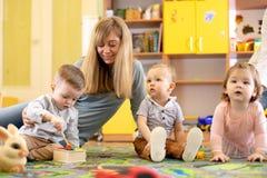 Учитель питомника смотря после детей в daycare Малыши маленьких ребят играют вместе с отработочными игрушками стоковые фотографии rf