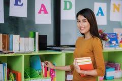 Учитель подготавливает книгу для учит студенту в preschool Стоковое Фото