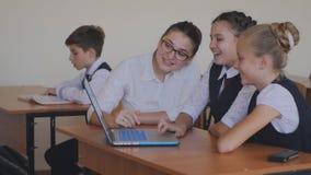 Учитель помогает студентам сделать задачу на ноутбуке Урок в классе компьютера видеоматериал