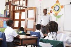 Учитель приветствует детей сидя в классе начальной школы Стоковые Изображения RF