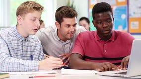 Учитель при 2 мужских студента средней школы работая на компьтер-книжке в классе