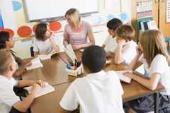 учитель ребенокев школьного возраста чтения типа их стоковое фото