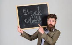 Учитель рекламирует назад к изучать, начинает учебный год Человек учителя бородатый стоит и держит классн классный с надписью стоковое изображение rf