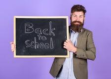 Учитель рекламирует назад к школьным принадлежностям покупки школы новым Человек учителя бородатый стоит и держит классн классный стоковые фотографии rf