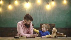 Учитель со стильными усиком и бородой и небольшой ребенк писать письма в тетради с прописями Милый мальчик рисуя изображение с сток-видео