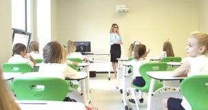 Учитель спрашивая детям на уроке на школе Высококачественный отснятый видеоматериал 4k видеоматериал