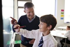 Учитель средней школы с формой студента нося используя взаимодействующее Whiteboard во время урока стоковая фотография