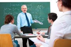 Учитель с студентами в классе стоковое изображение