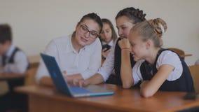 Учитель учит, что студенты работают на ноутбуке Урок в классе компьютера акции видеоматериалы