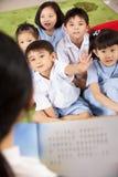 Учитель читая к классу студентов стоковые изображения