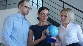 3 учителя обсуждают что-то с глобусом видеоматериал
