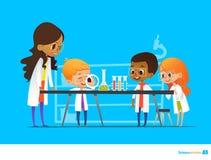 Учительница демонстрирует завод в склянке, детях смотрит через увеличитель на ей во время урока ботаники preschool Стоковое Изображение