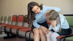 Учительница сидит утешающ девушку молодой школы унылую в коридоре акции видеоматериалы