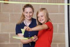 Учитель давая женский урок бадминтона зрачка стоковое изображение