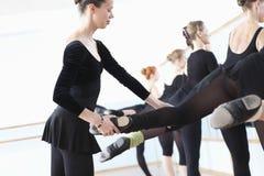 Учитель балета регулируя положения ноги балерин стоковое изображение