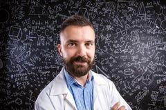 Учитель в белом пальто против большого классн классного с математически s Стоковые Фото