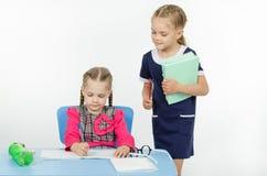 Учитель девушки во время задачи проверяет правильность своей вставки Стоковые Изображения RF