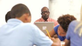 Учитель используя компьтер-книжку на столе как работа студентов акции видеоматериалы