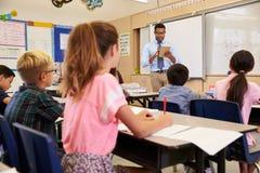 Учитель используя планшет в классе начальной школы Стоковая Фотография RF