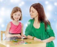 Учитель и девушка на таблице изучая карточки Стоковая Фотография