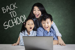 Учитель и дети с компьтер-книжкой в классе Стоковое Изображение