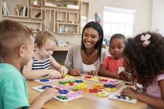 Учитель и зрачки используя формы цветка в школе Montessori стоковое фото rf