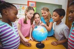 Учитель и зрачки смотря глобус стоковая фотография