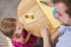 Учитель и зрачок используя деревянные формы в школе Montessori стоковая фотография
