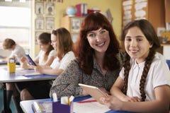 Учитель и школьница используя планшет смотрят к камере стоковая фотография