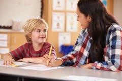 Учитель начальной школы в классе на столе с школьником стоковое изображение