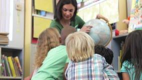 Учитель показывая группу в составе элементарный глобус школьников времени акции видеоматериалы