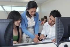 Учитель помогая студентам в лаборатории компьютера Стоковое Фото