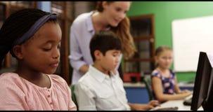 Учитель помогая школе ягнится на персональном компьютере в классе акции видеоматериалы