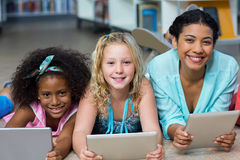 Учитель при девушки используя цифровые таблетки в библиотеке Стоковые Фотографии RF