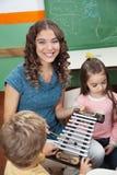 Учитель при дети играя ксилофон внутри Стоковые Фотографии RF